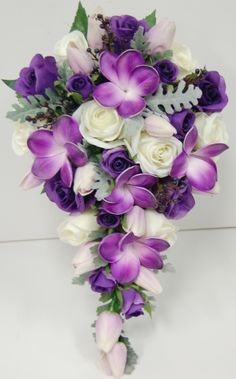 Purple tulips frangipanies cream roses with berries . simple teardrop bouquet