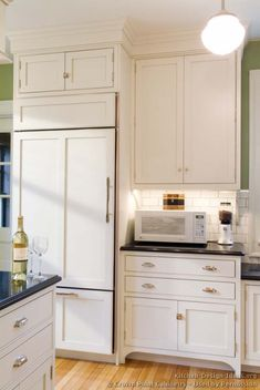 #Kitchen Idea of the Day: White kitchens brighten up the home. (By Crown Point Cabinetry). Gorgeous, white island tile backsplash panelized refrigerator