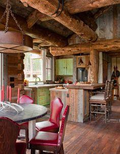 cuisine campagne avec un revêtement de sol en bois, meubles en bois, plafond à poutres apparentes et chaises rouges comme accent