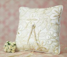 """This stunning ring pillow is layered with premium soft ivory satin with delicate gold embroidery accented with faux pearls and sequins. <br /> <br />Measures 7.5"""" x 7.5"""""""