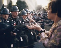 """Vietnam war protest. """"La Jeune Fille a la Fleur,"""" a photograph by Marc Riboud, shows the young pacifist Jane Rose Kasmir planting a flower on the bayonets of guards at the Pentagon during a protest against the Vietnam War on October 21, 1967. The photograph would eventually become the symbol of the flower power movement."""