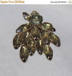 This #vintage smoky green rhinestone brooch is gorgeous.  It features a silver tone swedge style cluster in the Juliana style filled with marquise and round shaped smoky rhi... #ecochic #etsy #jewelry #jewellery