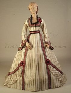 C. 1860, Dress of white silk gauze with black and red stripes. Bodice with square neck trimmed with black lace with red silk band in middle ...