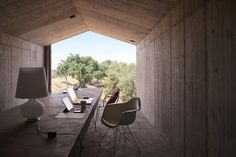 Amidst the old cork trees grasping onto the hills of Portugal's Alentejo region, Villa Além was constructed largely out of reddish concrete native to the area.