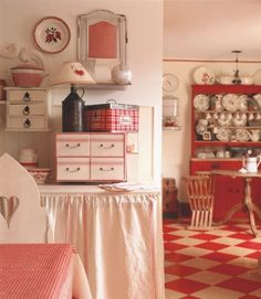 A red hand-painted checkerboard floor underscores this kitchen's playful mood: Finished in a muted shade of red, a cupboard houses prized pieces of china, while colorful storage items and a counter skirt crafted from dish towels brighten the work area.