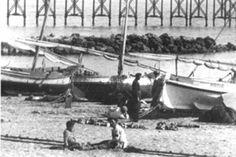 Junto a ellas, en la arena, los pescadores reparan las redes.