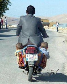 Homme en moto et ses enfants