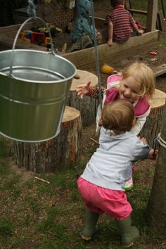 By adding a bucket & a rope to the outdoor area, you can create many, many opportunities for open-ended play, problem solving and cooperation. Not to mention great photo opportunities like this!