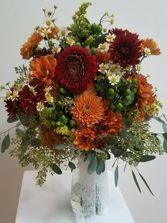 Fall wedding bouquet. red, orange and rust- Mums, fever few, hypericum berry, gerpoms, solidago, and seeded eucalyptus
