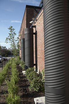 The Green Building by (fer) studio, LLP; Where storm water does flow off the green roof, the three collection tanks on the west side collect up to 240 cubic feet of the flow. The water is then reused for irrigation and outdoor purposes.