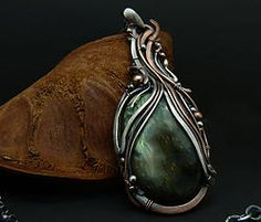 Aurora Falls - Pendant Necklace with Labradorite, This dramatic pendant created with copper and fine silver that represent the flow of the suns breath. Gently cradling a majestic Labradorite gemstone that flashes with the beauty of the aurora lights.   Suspended from a sterling silver chain adorned with labradorite stones and attached with a hand forged copper clasp.