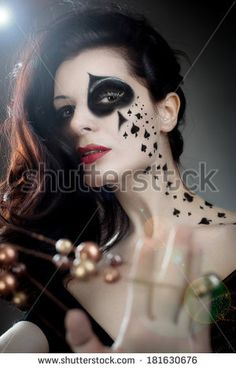 beautiful woman with make-up and body-art styled as playing card queens by shmel, via Shutterstock