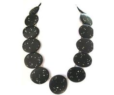 Black beach stone starry night necklace inlaid with sterling silver and white (lab grown) sapphires.  The necklace is approximately 18 inches long and has a toggle closure.  It is very light and a definite statement piece!