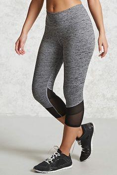 An athletic pair of knit leggings featuring a marled pattern, capri cut, mesh-insert hem, and a back zip key pocket.