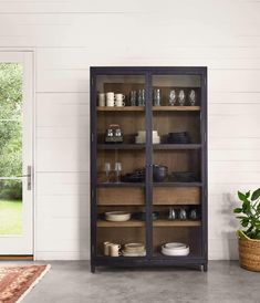 Two-tone transparency. Black drifted oak frames lighter interior shelving for subtle but striking contrast. This glass door cabinet provides great storage. Wood Shelves, Shelving, Glass Shelves, Crockery Cabinet, Dining Cabinet, Entryway Cabinet, Tempered Glass Door, Frame Light, Glass Cabinet Doors