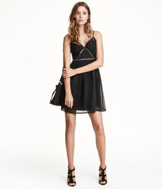 Short, V-neck dress in crinkled chiffon. Bodice with braided trim intertwined with metal rings and narrow adjustable shoulder straps. Low-cut V-neck, hook-and-eye fasteners, and concealed zip at back. Gently flared skirt. Lined.