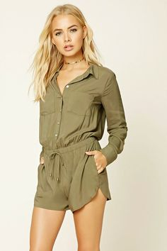A woven romper featuring a button front, a basic collar, four pocket construction, an elasticized drawstring waist, long sleeves with button cuffs, and a dolphin hem.