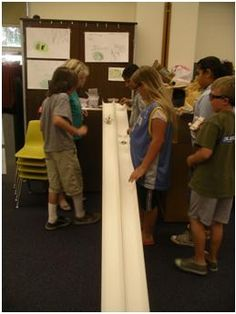 Photo shows students testing their model cars on two side-by-side tracks angled from a tabletop to the floor.