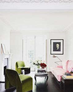 French living space with dark wood floors, a pink sofa, a vintage coffee table, and modern green velvet armchairs