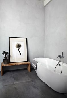 Minimalist bathroom, large black tile, concrete walls, modern freestanding tub, bench in bathroom, modern bathroom
