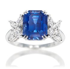 Harry Winston Marquesa Sapphire Ring. Emerald-cut sapphire, 4.99 carats; 8 marquise and pear-shaped diamonds, 1.10 total carats; platinum setting.