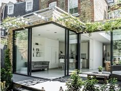 Charles Barclay Architects | This London home has sliding floor-to-ceiling glass doors that open the living room and kitchen to the surrounding garden terrace. In spring and summer, the fresh scent of roses climbing over the trellis fills the home.