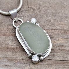 """Sea glass pendant crafted from a piece of genuine sea glass is captured in an original setting of tarnish resistant sterling silver and accented with a sparkly 3mm and 4mm CZs (cubic zirconia). The pendant measures approximately 1 1/2"""" from the top of the bail to the bottom of the pendant and 1\3/4"""" wide."""