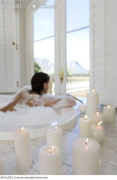 Young woman in bubble bath, illuminated candles in foreground: visualphotos.com