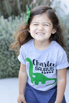 This is such a sweet personalized shirt for your little dinosaur lover! This tee is designed to be a girls tee.  Find our boys dino tee here: https://www.etsy.com/listing/289279419/boys-dinosaur-shirt-dinosaur-tee-t-rex?ref=listings_manager_grid  Shirt Details: Choose from a gray, white, or black soft jersey short-sleeved shirt. Crew and v-necks styles are available depending on the color tee youd like.  Heat transfer vinyl is pressed onto the shirt. Sparkly ...