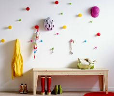 Colorful knobs attached at different heights to a hallway wall with child's clothes and accessories hanging from them and a bench with shoes underneath in front