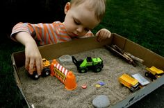 Sensory play in a cardboard box - Create a small world by adding sand, vehicles, rocks or glass beads, etc. (happy hooligans)