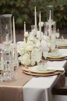 Gold runners, white linens, goblets with succulents and pillar candles