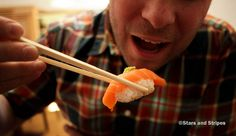 Stars and Stripes photographer Joshua L. DeMotts gets ready to devour a piece of salmon nigiri sushi at Ayame, a Japanese restaurant in Kaiserslautern. (Matt Millham/Stars and Stripes)