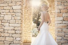 Influenced by the fashion houses of Europe, this statement-making fit and flare Pearl Mikado wedding gown from Essense of Australia features gorgeous, hand-sewn Diamantes on its shoulder straps, keyhole back and waist. The back zips up under alternating fabric and Diamante buttons. (sp)