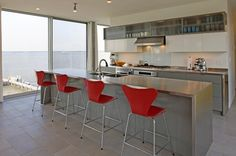 Stainless steel kitchen island with red Series 7 stools