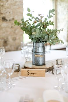 Rustic milk churn centrepiece with eucalyptus on a wood slice with brass tea light holders and a wooden table number. All on top of a hessian and lace table runner. Wedding styling at Healey Barn in Northumberland. Burlap Table Settings, Round Table Settings, Burlap Lace Table Runner, Wedding Table Settings, Round Wedding Tables, Wedding Top Table, Rustic Round Table, Barn Wedding Centerpieces, Wedding Decorations