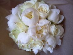 Ivory bridal handtied bouquet of Avalanche roses and paeonies with topaz Swarovski crystals.  For more wedding flowers inspiration please visit http://thefineflowerscompany.co.uk