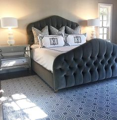 Chic gray bedroom features a gray velvet tufted bed with footboard dressed in black and white monogrammed Greek key shams and duvet flanked by mirrored nightstands and white gourd lamps alongside a gray geometric rug.
