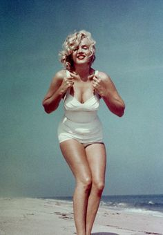 A curvaceous, red-lipped                          Marilyn Monroe                          poses on Amagansett Beach, Long Island while on holiday with husband Arthur Miller in 1957 for one of her most iconic editorials shot by Sam Shaw.