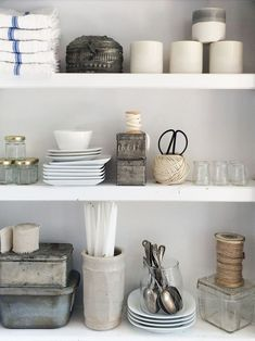 Kitchen shelf styling. Candles in ceramic ha, steel scissors in twine, folded dish towels. Mix of glass, steel, stone and porcelain. Vintage spoons in glass vessel.