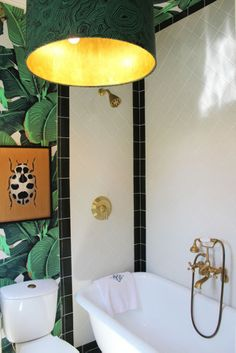 Bathroom, banana leaf Martinique wallpaper, brass faucet, black white tile, green malachite gold pendant