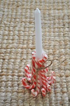 To make it, wrap a rubber band around a candle and insert the candy canes around the candle under the rubber band. Tie a piece of ribbon around them and then remove the rubber band.  Can also use a pillar candle & peppermint sticks.