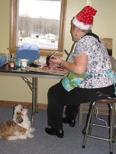 Tibby, the office mascot, patiently hopes Janelle drops a piece as she carves the Christmas ham.