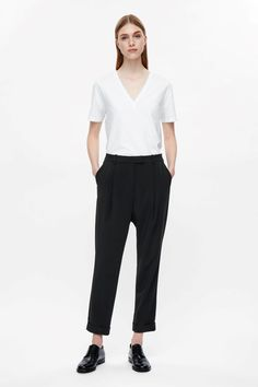 A tailored style, these tapered trousers are made from lightly textured, fluid fabric with soft pleats along the front. Cut to sit just below the waist and dropped at the crotch, they have front and back pockets and relaxed turn-up hems.