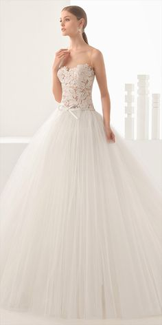 Princess-style dress with transparent lace bodice and full tulle skirt, in natural. Nieves transparent lace bodice with Dado skirt and sash.