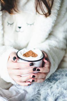 Foto aconchegante com pijama de ovelhinha segurando uma caneca com chocolate quente, chantilly e um coração feito de canela.