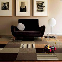 Ritmo - *repetição* de cores por todo o ambiente: o preto, o cinza e o bege estão no tapete, na poltrona e na parede, distribuindo o interesse horizontal e verticalmente. Muito *contraste* entre cores, direções das linhas, e entre formas livres como da poltrona e geométricas como dos quadros e tapete.