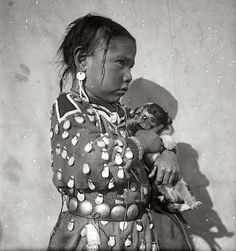 Blanket Bull's daughter with puppy. Crow. Early 1900s. Photo by Richard Throssel. Source/University of Wyoming (American Heritage Center)