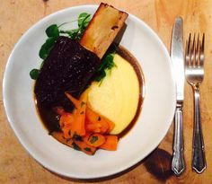 Slow roast Beef Short Rib, (braised in carrot, onion, thyme, rosemary, red wine, veal stock) on a bed of wet polenta (Parmesan & butter) with baby watercress & carrots with parsley.