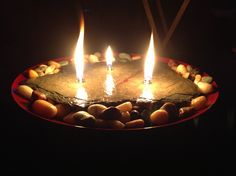 Candle my husband made out of slate, glass lamp wicks, lamp oil, glass votive cups, & rocks in a bowl